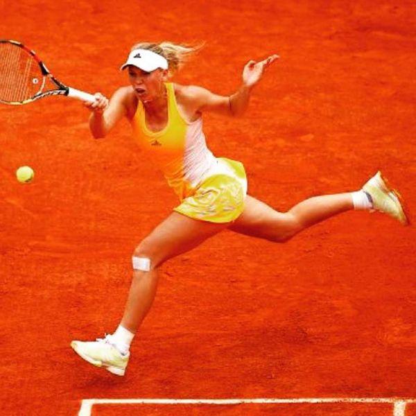 Caroline Wozniacki serves the ball back to Karin Knapp during their first round match